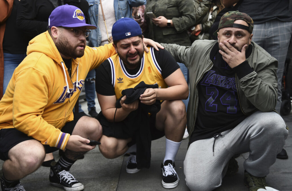 Los Angeles Lakers fans Alex Fultz, from left, Eddy Rivas and Rene Alfaro react to the death of former NBA player Kobe Bryant outside of the Staples Center prior to the 62nd annual Grammy Awards on Sunday, Jan. 26, 2020, in Los Angeles. Bryant died Sunday in a helicopter crash near Calabasas, Calif. He was 41. (AP Photo/Chris Pizzello)