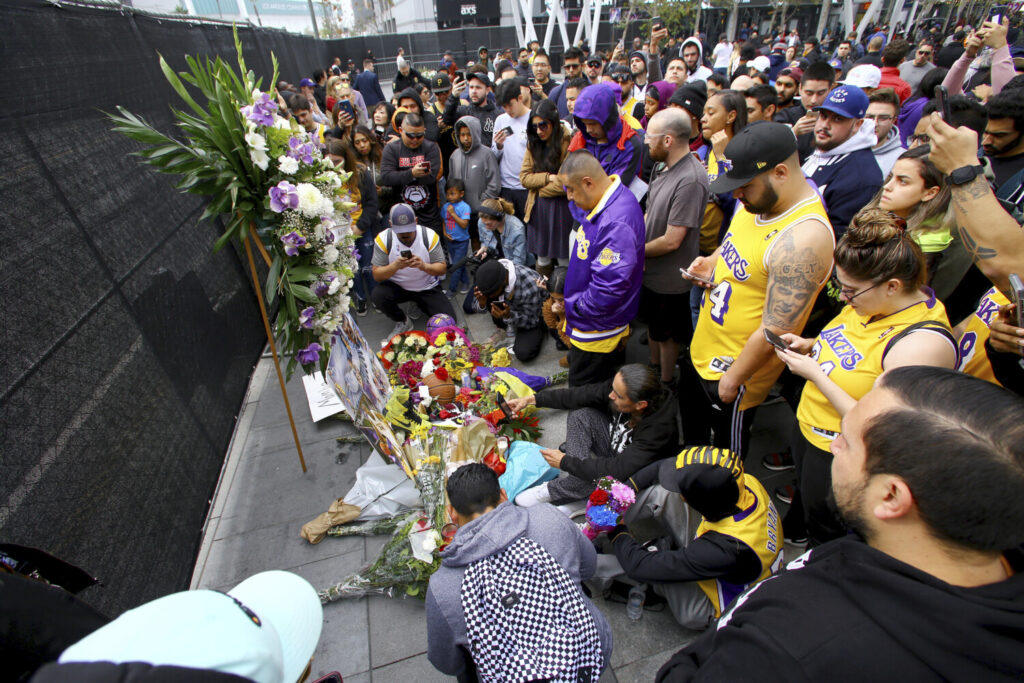 Fans of Kobe Bryant mourn at a memorial to him in front of Staples Center, home of the Los Angeles Lakers, after word of the Lakers star's death in a helicopter crash, in downtown Los Angeles Sunday, Jan. 26, 2020. (AP Photo/Matt Hartman)