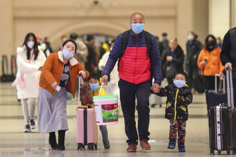 Travelers wearing face masks walk with their luggage at Hankou Railway Station in Wuhan in southern China's Hubei province. The U.S. on Tuesday reported its first case of a new and potentially deadly virus circulating in China.