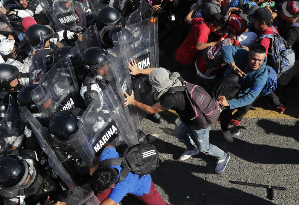 Migrants charge Mexican National Guardsmen at the border crossing in Tecun Uman, Guatemala, on Saturday.