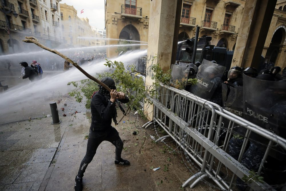 Anti-government demonstrators clash with riot police at a road leading to the parliament building in Beirut, Lebanon, on Saturday. Riot police fired tears gas and sprayed protesters with water cannons after riots broke out during a march against the ruling elite amid a severe economic crisis.