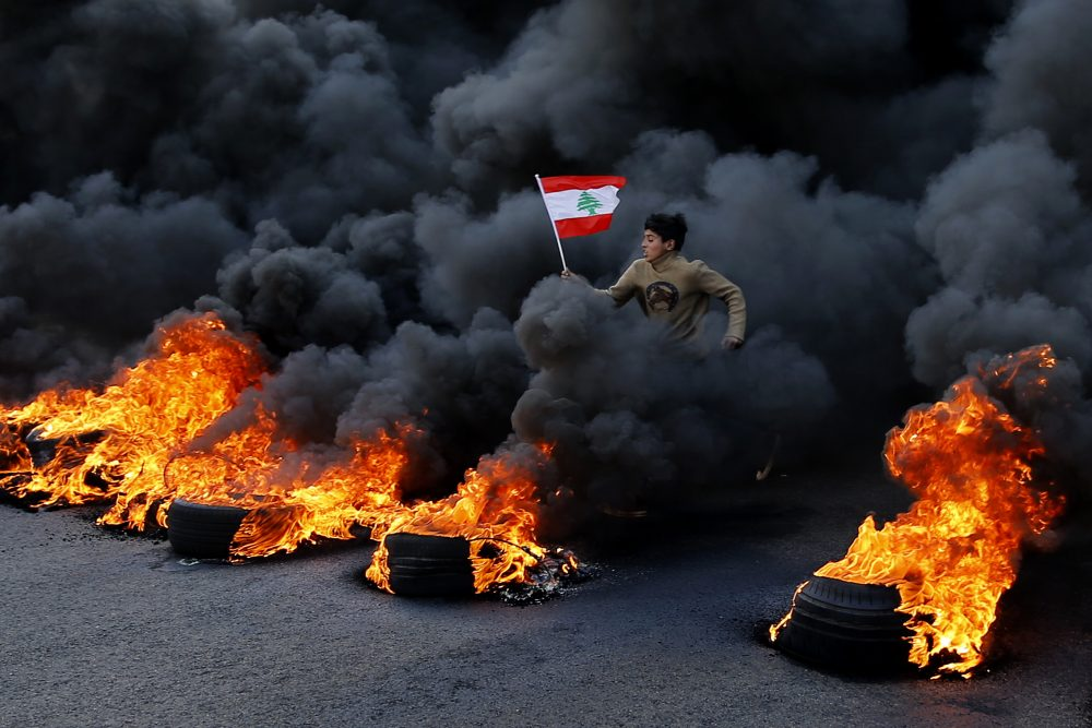 An anti-government demonstrator jumps on flaming tires to block a main highway during a protest in the town of Jal el-Dib, Lebanon, on Tuesday. Following a brief lull, Lebanese protesters returned to the streets in renewed rallies against a ruling elite they say has failed to address the economy's downward spiral.