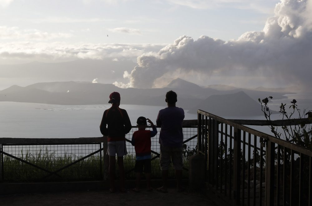 People watch from Tagaytay as Taal volcano continues to spew ash on Tuesday. Thousands of people fled the area through heavy ash as experts warned that the eruption could get worse and plans were being made to evacuate more.