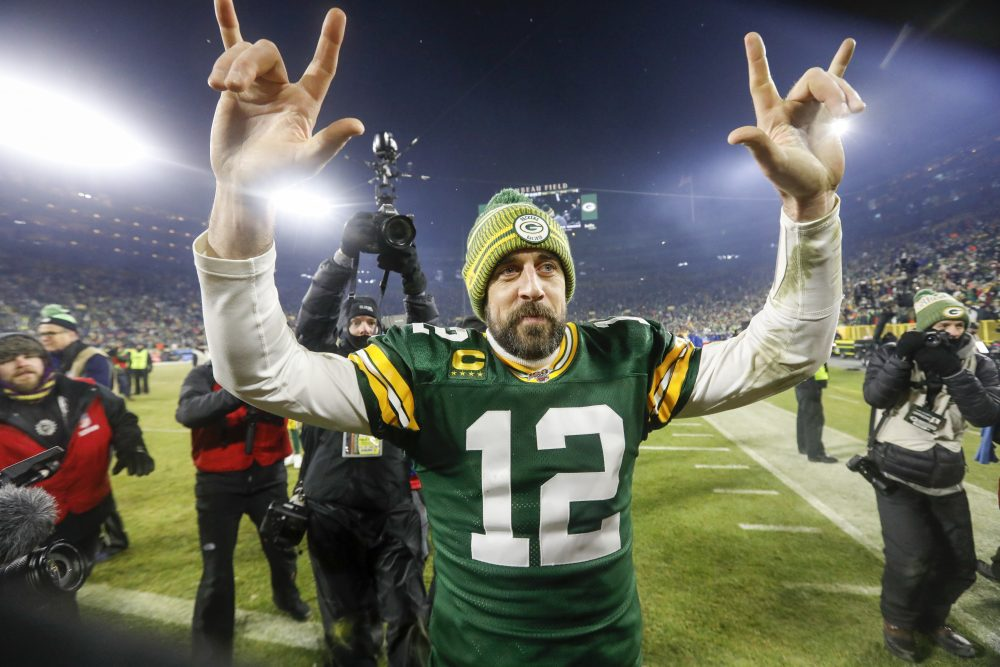 "Packers' quarterback Aaron Rodgers signs ""I love you"" to the Lambeau Field crowd after leading the Packers past the Seahawks and sending Green Bay to the NFC championship game."