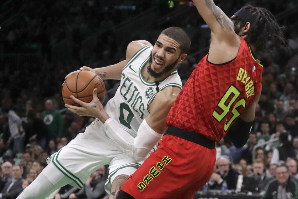 Jayson Tatum of the Celtics leans in as he drives against Atlanta's DeAndre' Bembry during Friday's game in Boston.