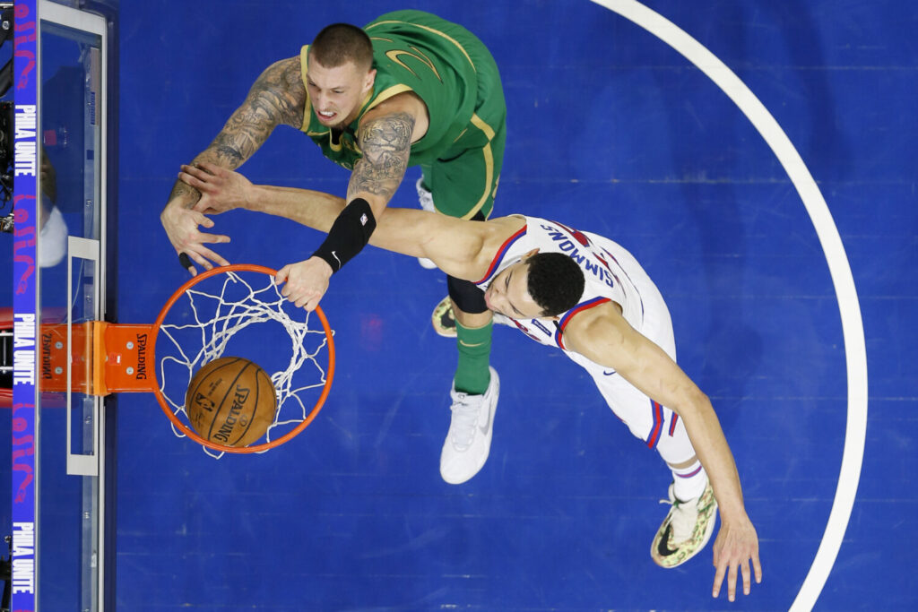 Boston's Daniel Theis, left, dunks against Philadelphia's Ben Simmons during Thursday's game in Philadelphia.