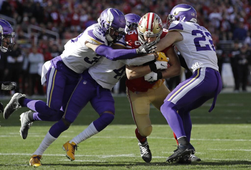 San Francisco tight end George Kittle, center, is tackled by Minnesota's Harrison Smith, right, and other defenders during Saturday's divisional playoff game. Kittle had just three catches for 16 yards, but the 49ers beat the Vikings, 27-10.