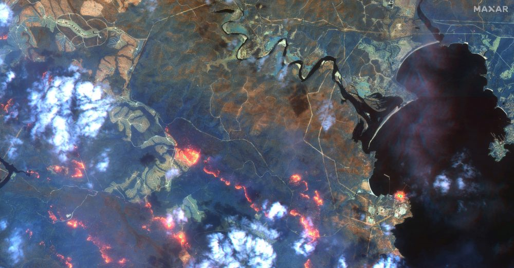This satellite photo  shows wildfires spreading in the area south of Eden and Twofold Bay, shown in black, in New South Wales state of Australia, on Sunday.