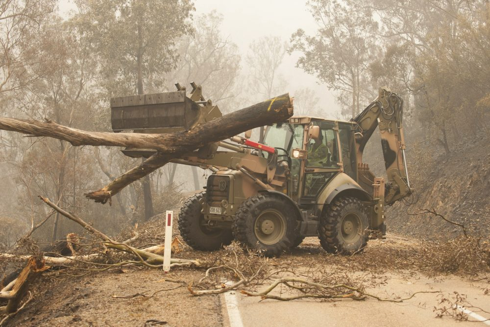 In this image released and dated on Jan. 6, 2020, from Australian Department of Defence, plant operators Cpl. Duncan Keith and Sapper Ian Larner of the 22nd Engineer Regiment use a 434 backhoe to assist staff from Forestry Management Victoria to clear fire damaged trees from the great Alpine road between Bairnsdale and Omeo during Operation Bushfire Assist 19-20 in Bairnsdale, Victoria, Australia.