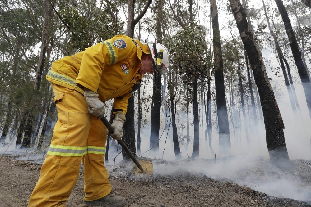 A firefighter uses a rake to manage a controlled burn near Tomerong, Australia, Wednesday, Jan. 8, 2020, in an effort to contain a larger fire nearby.
