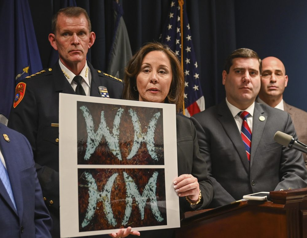 Suffolk County Police Commissioner Geraldine Hart shows a photograph with the initials on a belt, showing either an HM or WH, depending on the angle, during a press conference at police headquarters in Yaphank , N.Y., in January.