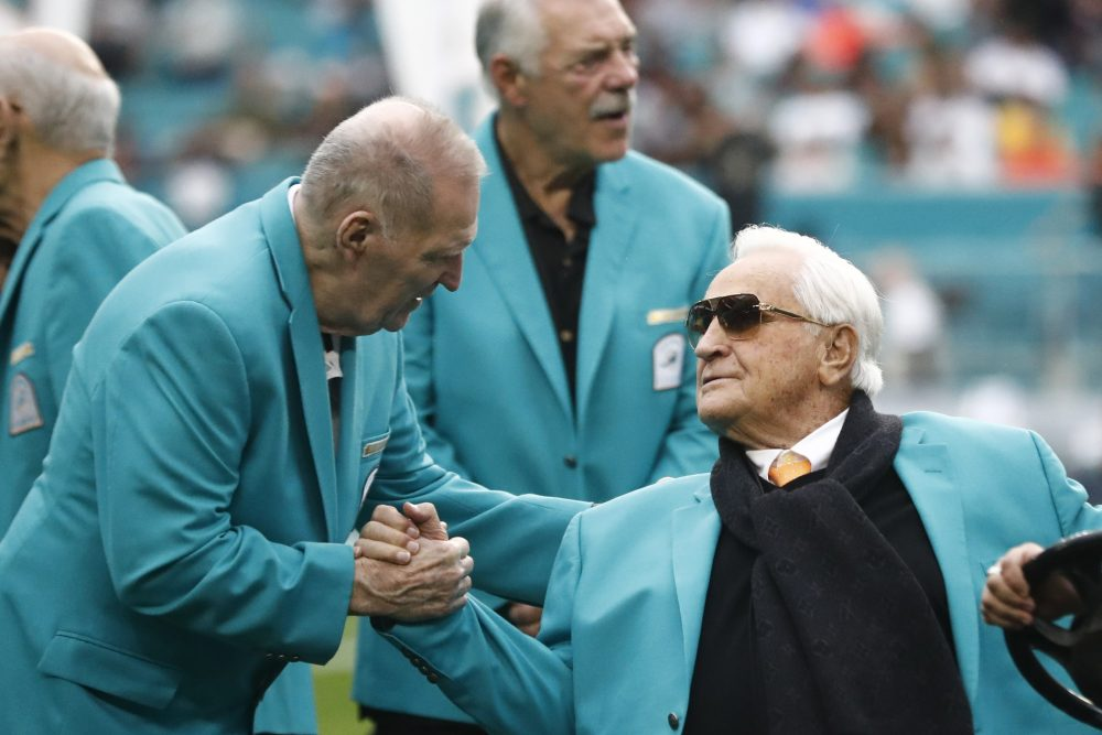 Former Miami Dolphins head coach Don Shula is greeted on the field by former players.