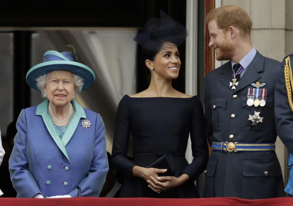 Britain's Queen Elizabeth II, and Meghan the Duchess of Sussex and Prince Harry watch a flypast of Royal Air Force aircraft pass over Buckingham Palace in London on July 10, 2018. Royal officials said the queen had summoned her grandsons and their father to Sandringham Estate for a meeting on Monday.