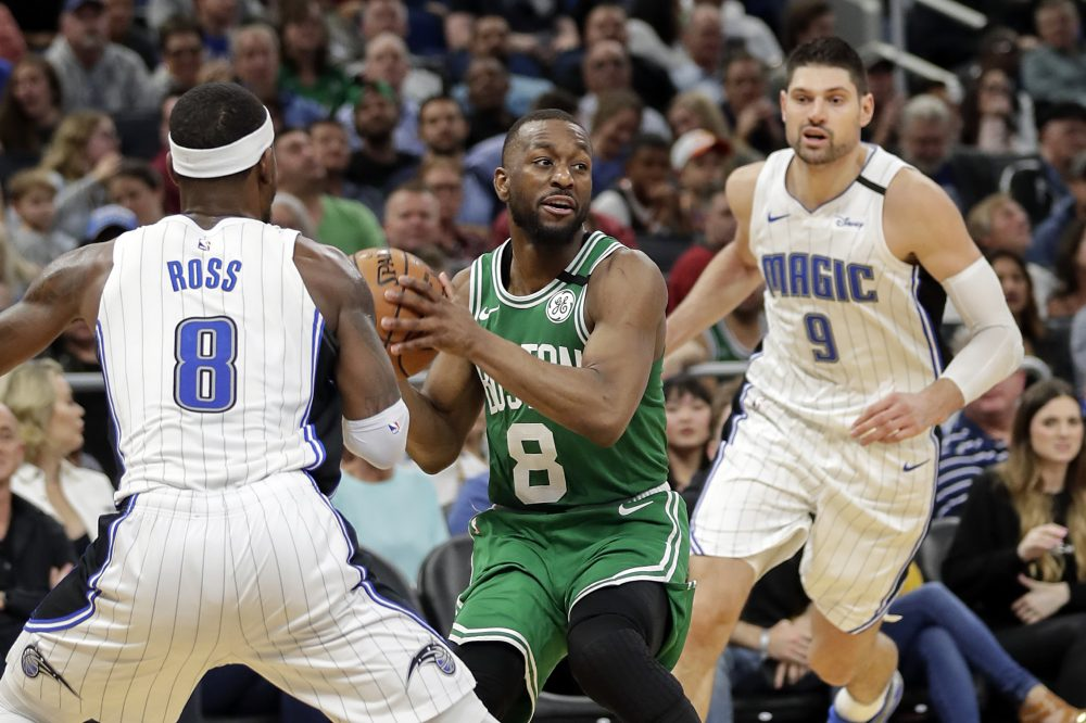 Celtics guard Kemba Walker, center, looks to pass the ball as he is defended by Orlando guard Terrence Ross, left, and center Nikola Vucevic during the Celtics' 109-98 win Friday in Orlando, Florida. Walker finished with 37 points.