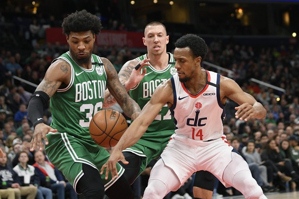 Celtics guard Marcus Smart, left, forward Daniel Theis, center,  and  Wizards guard Ish Smith  battle for the ball during Washington's 99-94 win Monday in Washington.