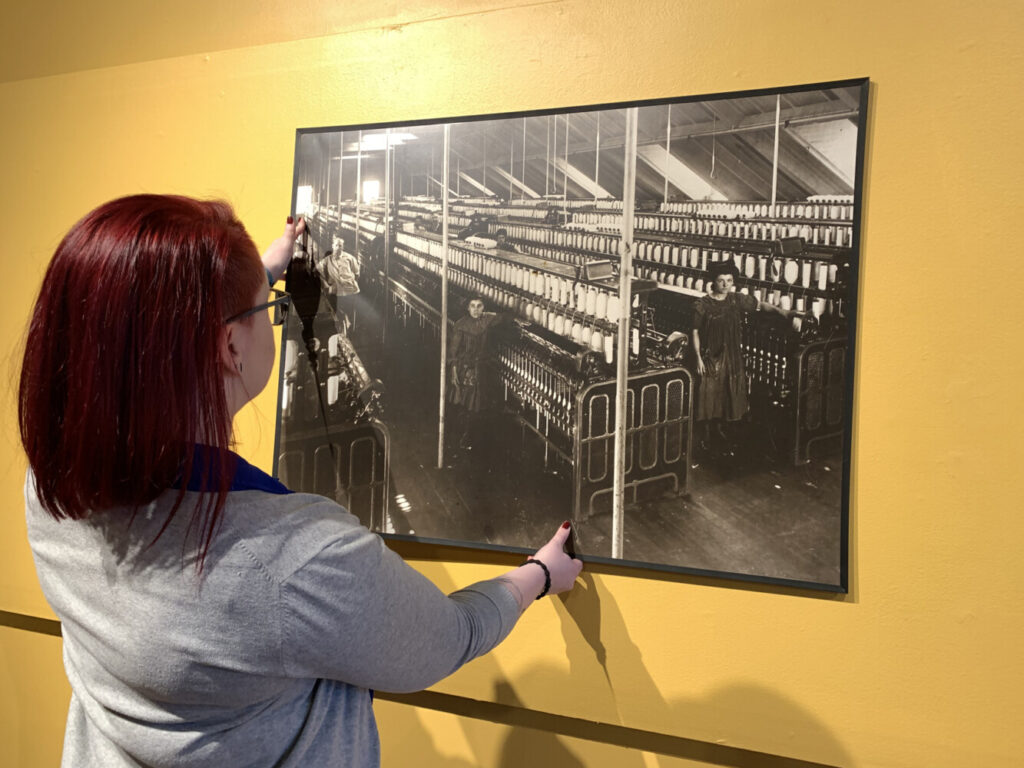 """Emma Sieh, collections and exhibits coordinator at Museum L-A, installs one of the reproduction photographs of children working in the textile mills in the gallery for the upcoming child labor exhibit """"All Work and No Play"""" that opens January 30. The reproduction is on loan from the USM Franco American Collection."""