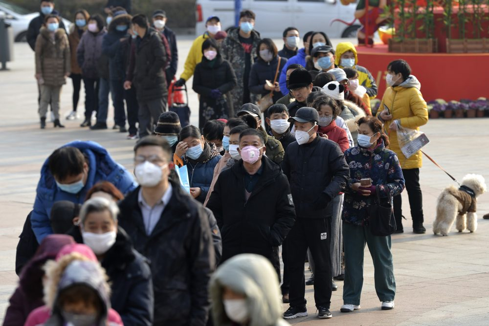 People line up to buy face masks at a drug store Wednesday in Nanjing in eastern China's Jiangsu Province. Countries began evacuating their citizens Wednesday from the Chinese city hardest-hit by an outbreak of a new virus that infected more than 6,000 on the mainland and abroad.