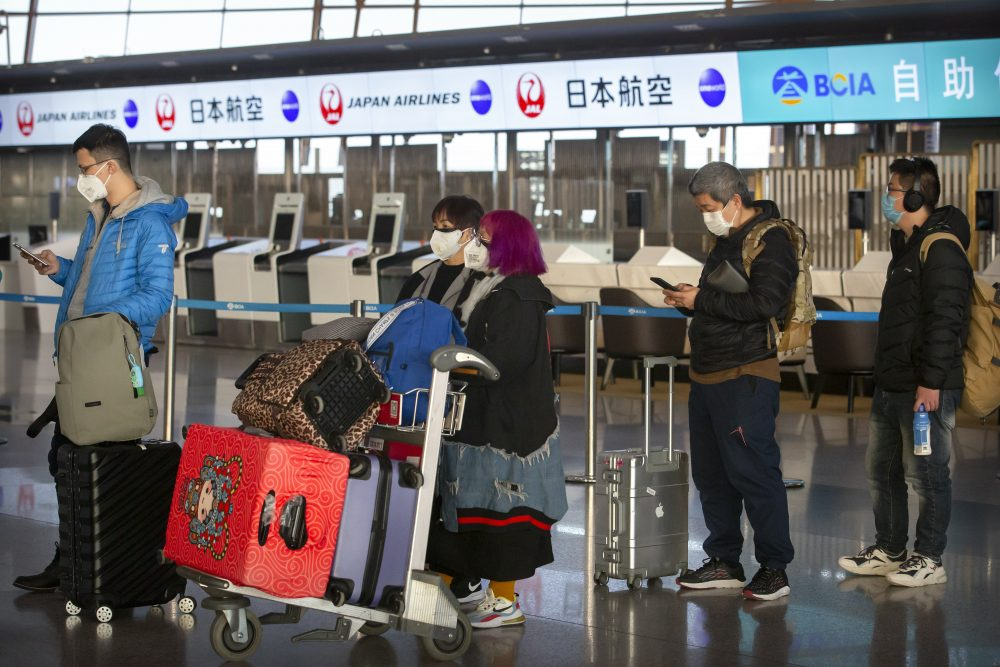 Travelers wearing face masks line up near the Japan Airlines check-in counters at Beijing Capital International Airport in Beijing, Thursday.