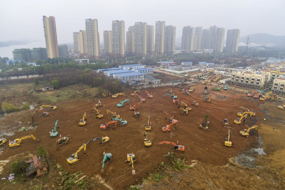 Heavy equipment works at a construction site for a field hospital in Wuhan in central China's Hubei Province, where the coronavirus outbreak origniated. Chinatopix via AP