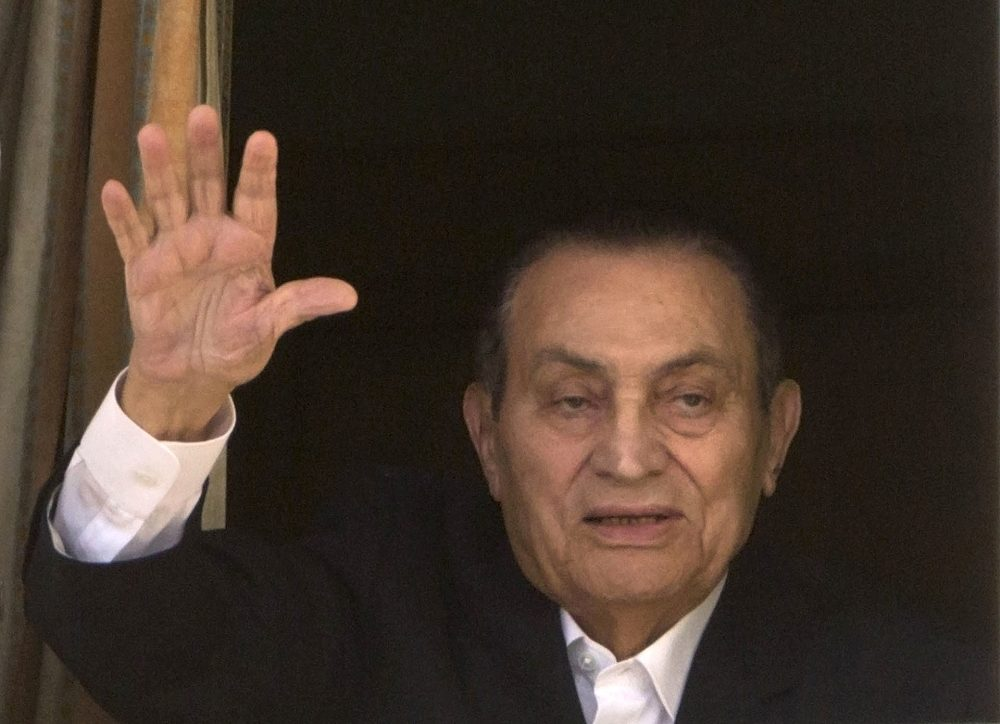 Ousted Egyptian President Hosni Mubarak waves to his supporters from his room at the Maadi Military Hospital, where he was hospitalized in Cairo in 2016.