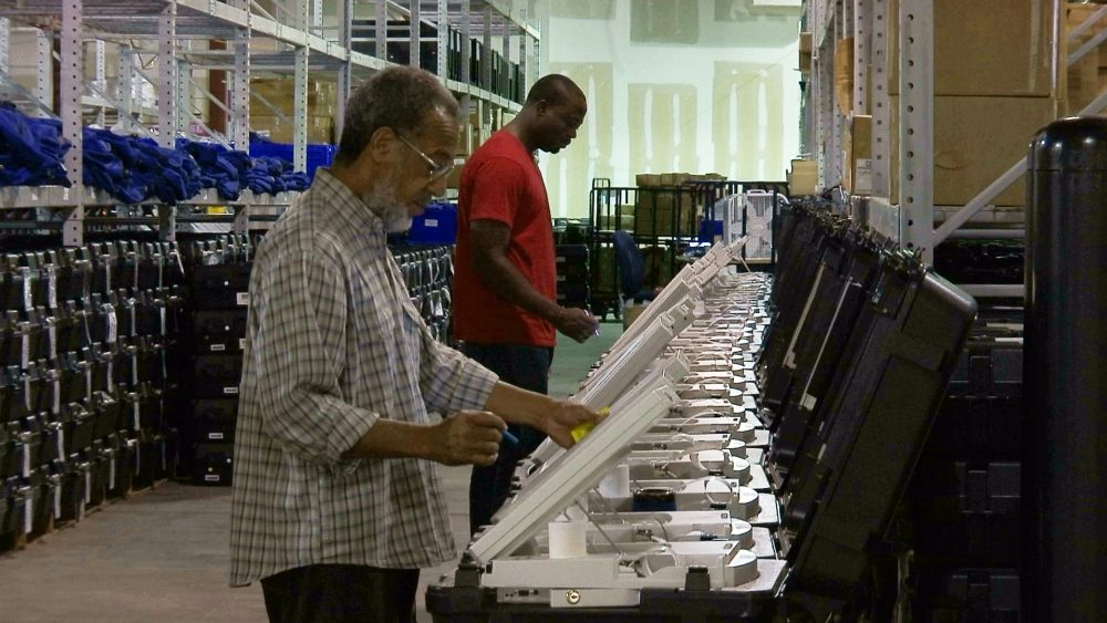 Employees of the Fulton County Election Preparation Center in Atlanta test electronic voting machines in 2016. A computer security expert says he found that an election server central to a legal battle over the integrity of Georgia elections showed signs of tampering.