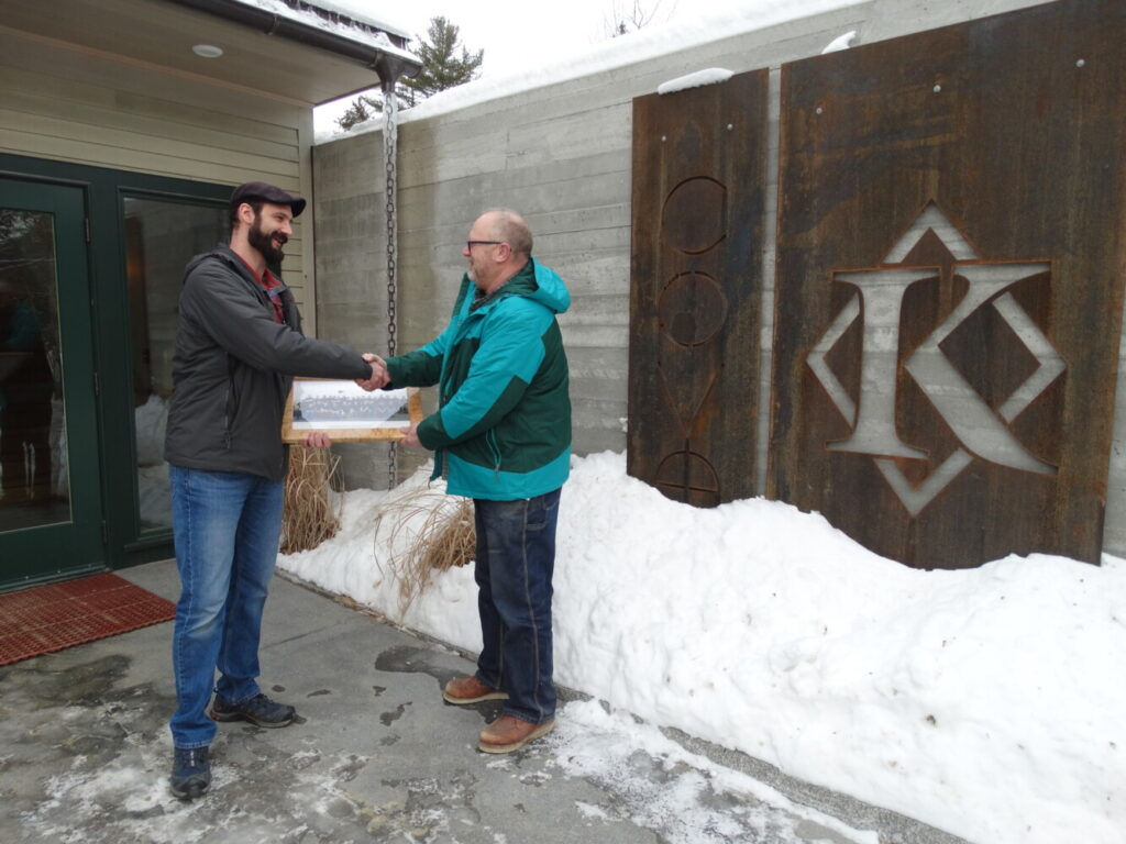 Capital Area Technical Center Building Construction Instructor Tom Holzwarth, right,  presented Greg Buzzell, left, from Knickerbocker Group in Boothbay, a plaque of appreciation for their company donation. The donation was a 2,000 board lot of miscellaneous boards in different widths, lengths and species to be used on various student projects ata the Augusta technical center. The plaque presented is framed with birdseye maple from their generous donation.