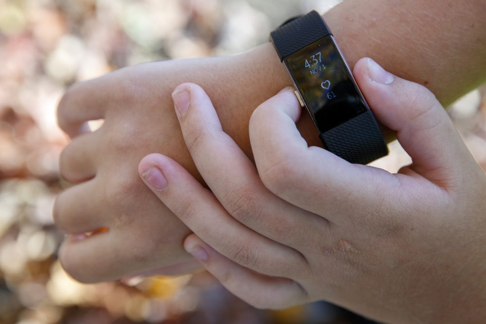 """Grace Brown, 14, adjusts her fitness tracker at the park where she does her jogging workouts for her """"online PE"""" class  Nov. 1 in Alexandria, Va. Brown chose to take """"online PE,"""" utilizing a fitness tracker, so that she could take a piano lab as an extra elective."""