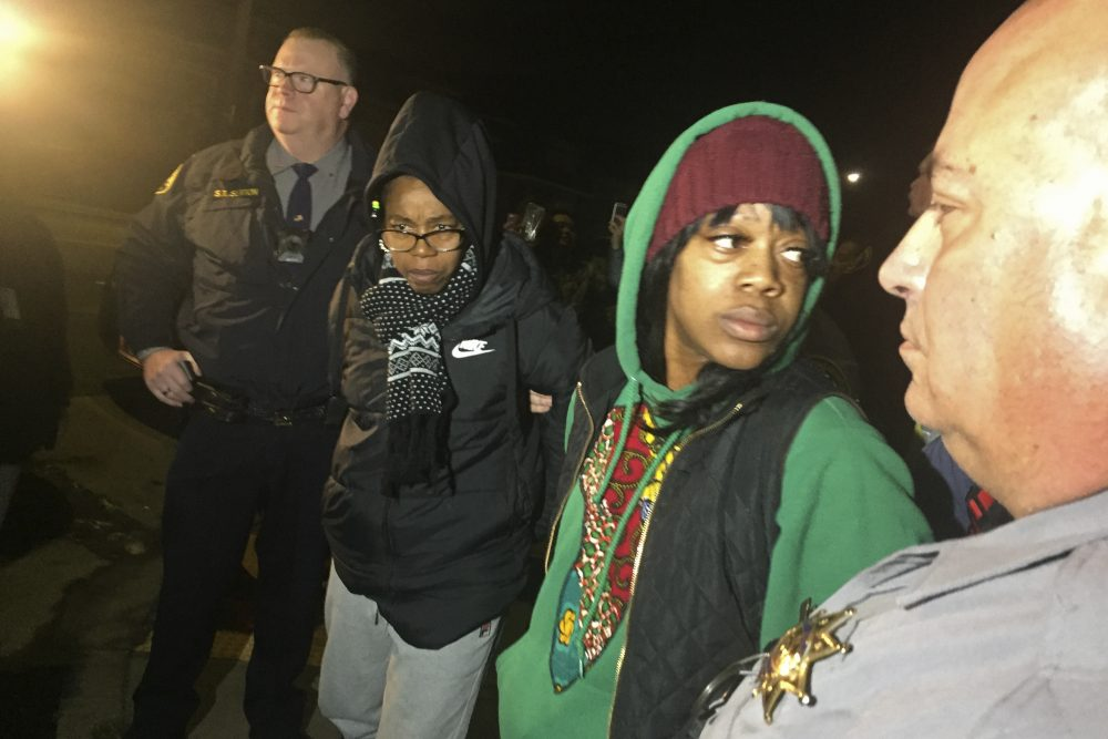 Tolani King, second from left, and Misty Cross are led away by Alameda County Sheriff's deputies after being removed from a house they were illegally occupying on Tuesday in Oakland, Calif. Police removed two women and a male supporter.