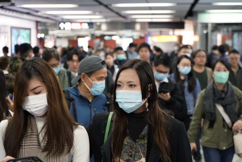 Passengers wear masks Wednesday to prevent an outbreak of a new coronavirus in a subway station in Hong Kong.