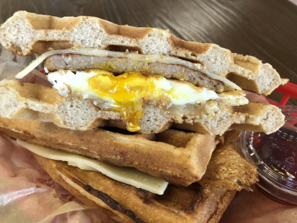 The Waffle is a breakfast sandwich with egg, sausage, cheddar cheese and maple syrup.