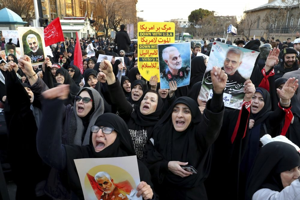 Protesters chant slogans while holding up posters of Gen. Qassem Soleimani during a demonstration Sunday in front of the British Embassy in Tehran, Iran.