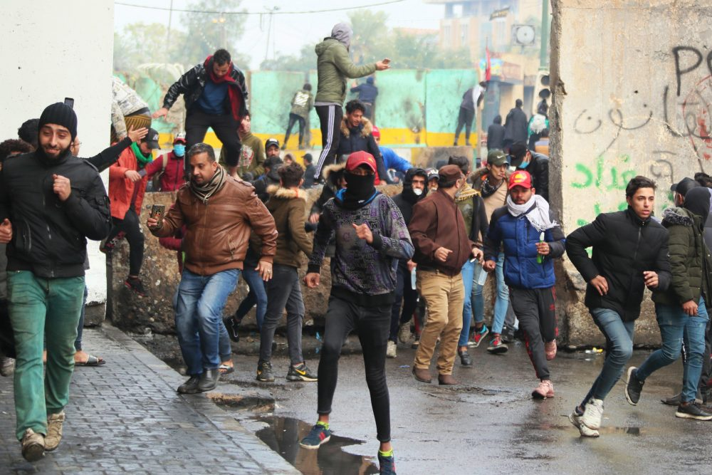 Anti-government protesters clash with security forces in Baghdad, Iraq, on Saturday.