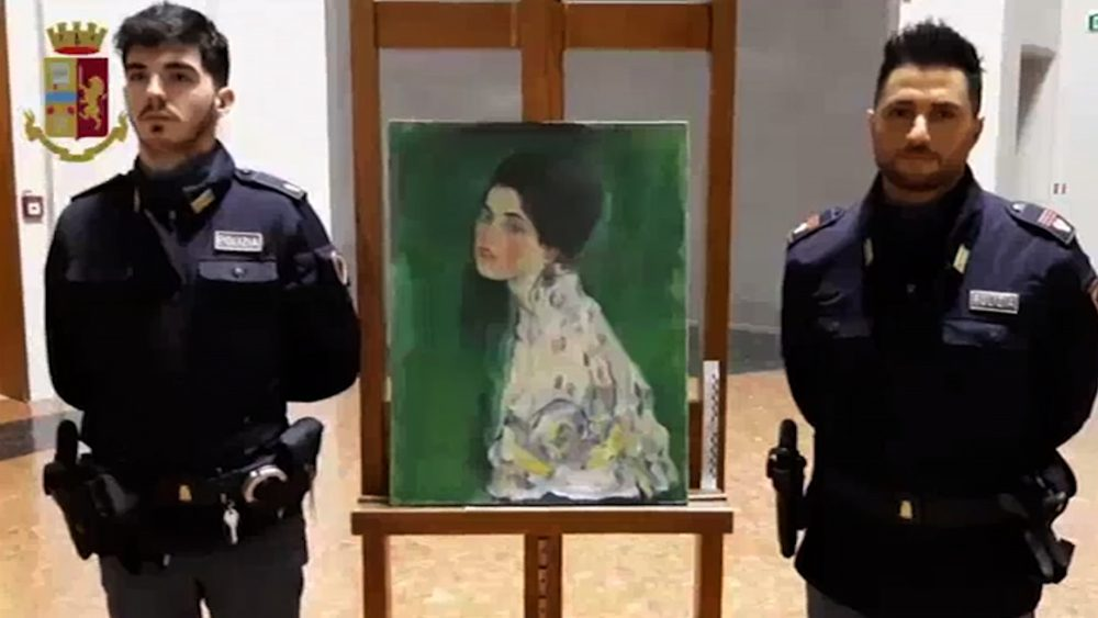 This image taken from a video distributed Wednesday by Italian police shows two police officers standing next to painting which was found inside a gallery's walls, in Piacenza, northern Italy.