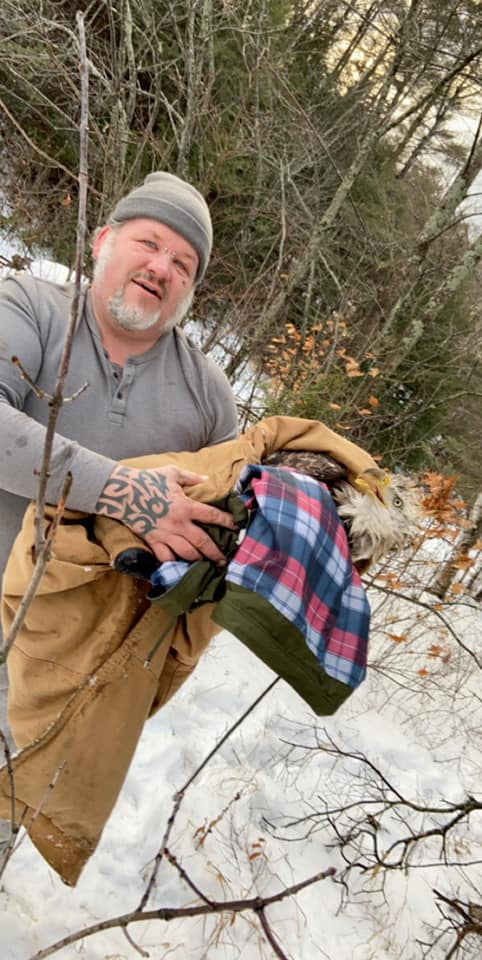 Jason Dolloff holds an injured bald eagle he and his daughter, Carrigan Robinson, rescued Sunday from the Androscoggin River in Peru.