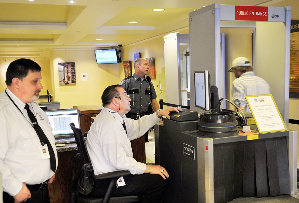 Capitol Police screeners review items while a visitor at the State House passes through a metal detector in 2013.
