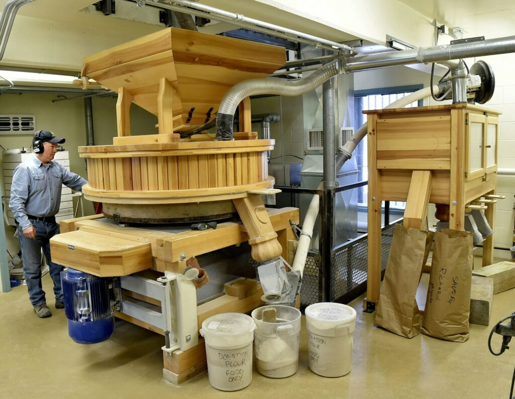 A huge millstone is used to grind flour inside the Grist Mill in Skowhegan last year. One of its associated businesses, Maine Grains, won two Good Food Awards at the San Francisco competition.