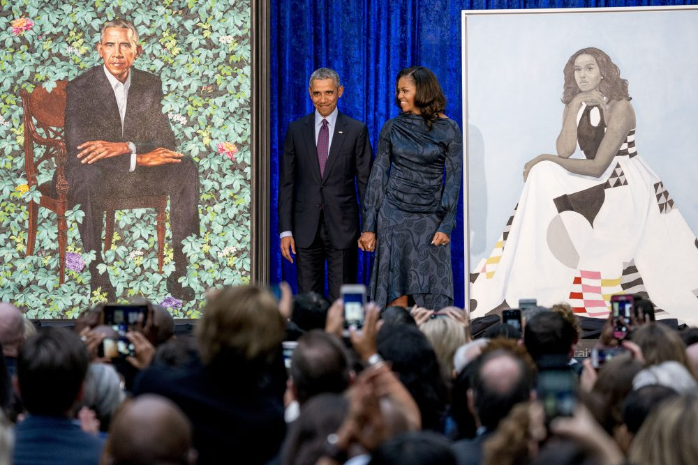FILE - In this Feb. 12, 2018, file photo, former President Barack Obama and former first lady Michelle Obama stand on stage together as their official portraits are unveiled at a ceremony at the Smithsonian's National Portrait Gallery in Washington. The portraits will begin a five-city national tour in Chicago in June 2021.