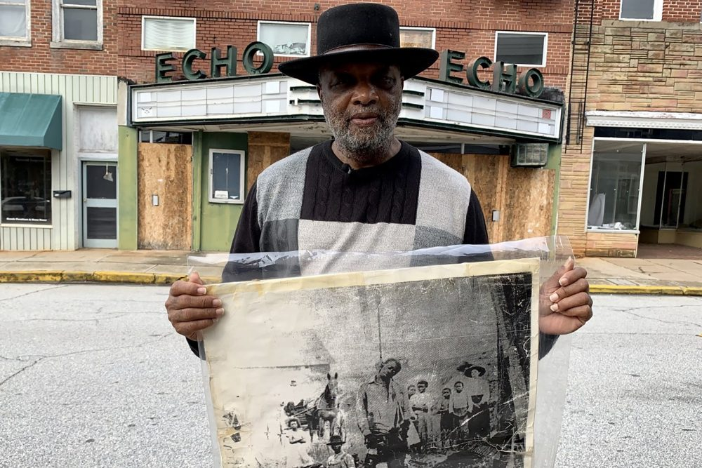 In this Monday, Jan. 13, 2020 photo, Rev. David Kennedy stands outside the Echo Theater holding a photo of his great uncle's lynching, in Laurens, S.C. Kennedy has fought for civil rights in South Carolina for decades.