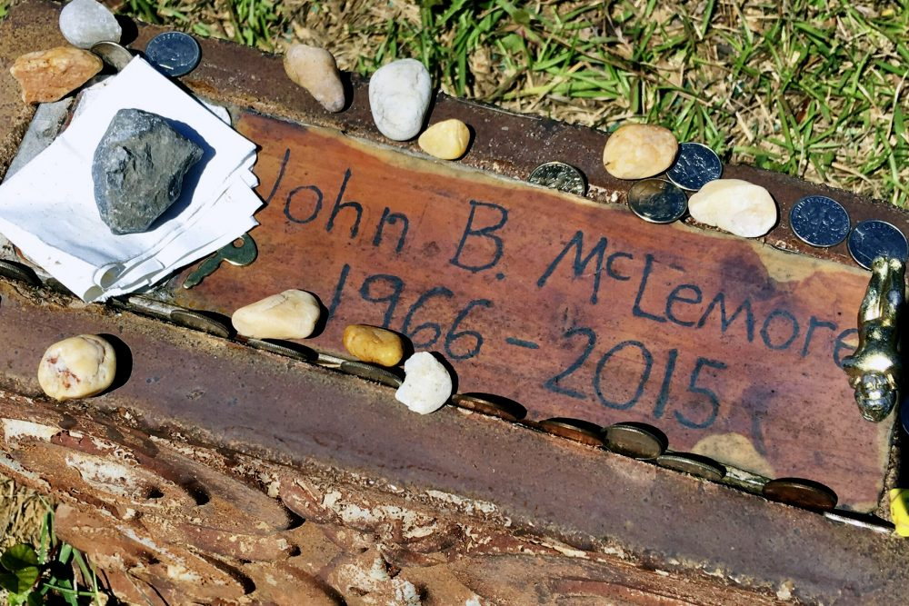 "This May 3, 2017, file photo, shows the grave of John B. McLemore in Green Pond, Ala., who is featured in the serialized podcast ""S-Town."" WIAT-TV reported that lawyers for the estate of McLemore, the key character in ""S-Town,"" and attorneys for the producer have selected a mediator to work on a settlement."