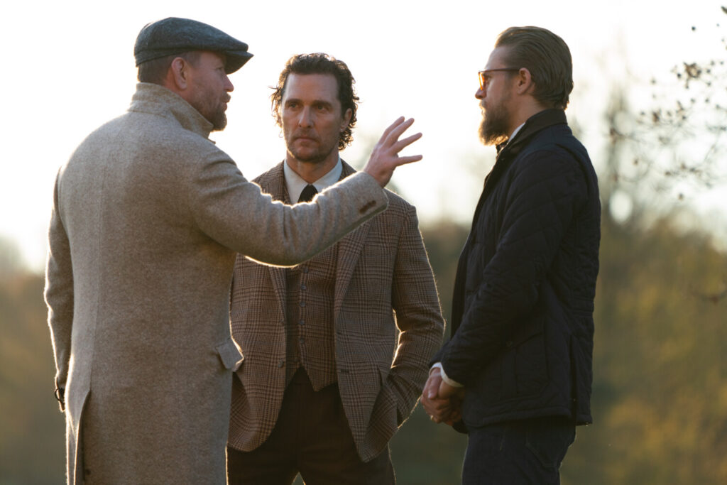 "Director Guy Ritchie, left, talks about a scene of  in ""The Gentlemen"" with Matthew McConaughey, center, and Charlie Hunnam."