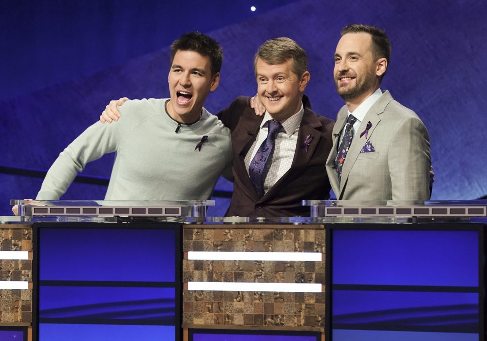 """Contestants, from left, James Holzhauer, Ken Jennings and Brad Rutter appear on the set of """"Jeopardy! The Greatest of All Time,"""" in Los Angeles. The all-time top """"Jeopardy!"""" money winners; Rutter, Jennings and  Holzhauer, will compete in a rare prime-time edition of the TV quiz show, which will air on consecutive nights beginning 8 p.m. Tuesday."""