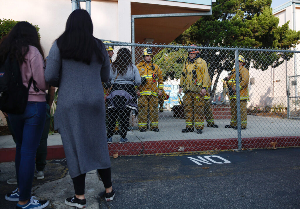 Parents wait outside Park Avenue Elementary School in Cudahy, Calif., after an airplane returning to Los Angeles International Airport dropped what was believed to be engine fuel onto a school playground Tuesday.