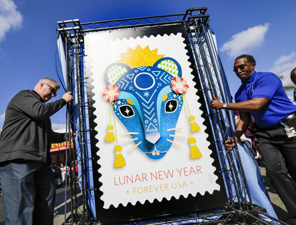 Michael Henry, left, and Charles Williams of the U.S. Postal Service with a replica of the Year of the Rat stamp at the Lunar New Year Festival in Monterey Park on Saturday.