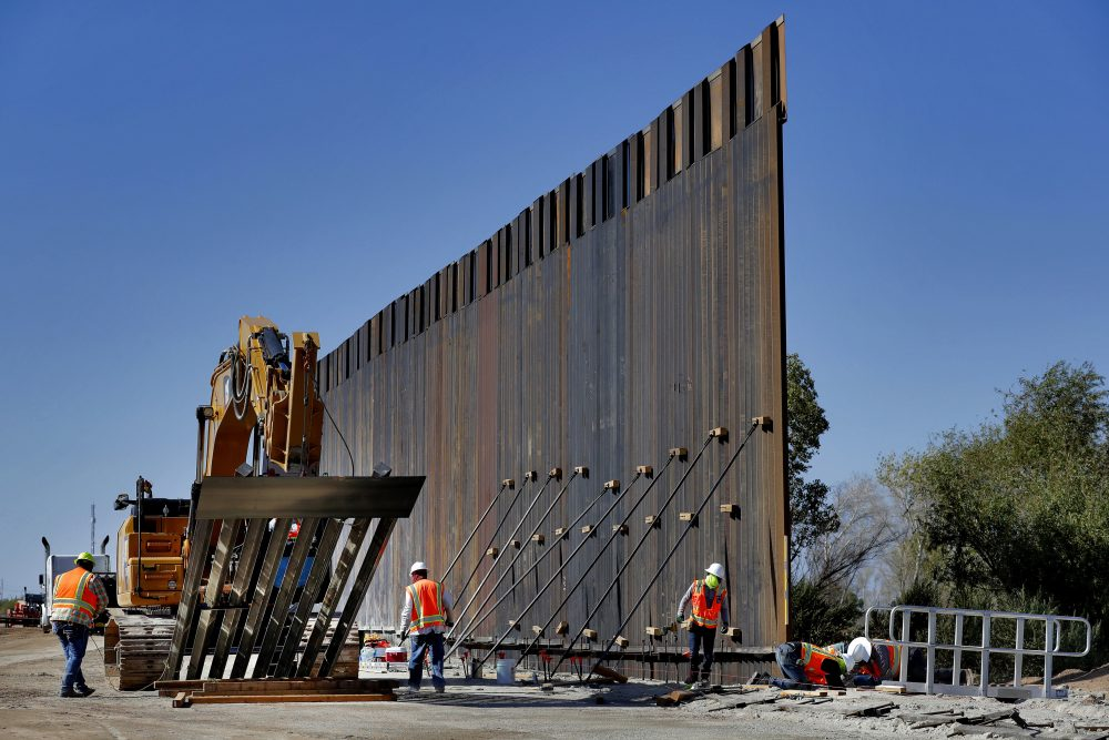 Government contractors erect a section of Pentagon-funded border wall along the Colorado River in Yuma, Ariz., in September. The White House says construction of the U.S.-Mexico border wall will move forward after a federal appeals court ruling that frees up construction money.