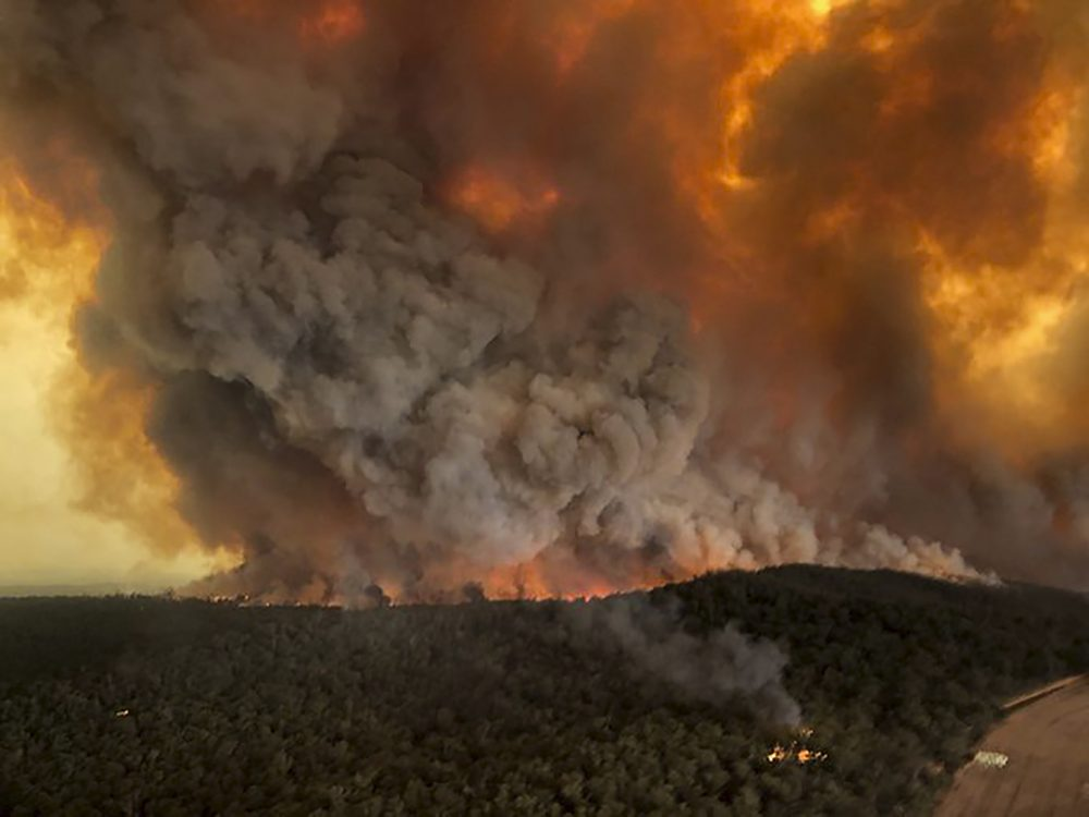 FILE - In this Monday, Dec. 30, 2019, aerial file photo, wildfires rage under plumes of smoke in Bairnsdale, Australia. U.S. officials said Tuesday, Jan. 7, 2020 they planning to send at least 100 more firefighters to Australia to join 159 already there battling blazes that have killed multiple people and destroyed thousands of homes. (Glen Morey via AP, File)