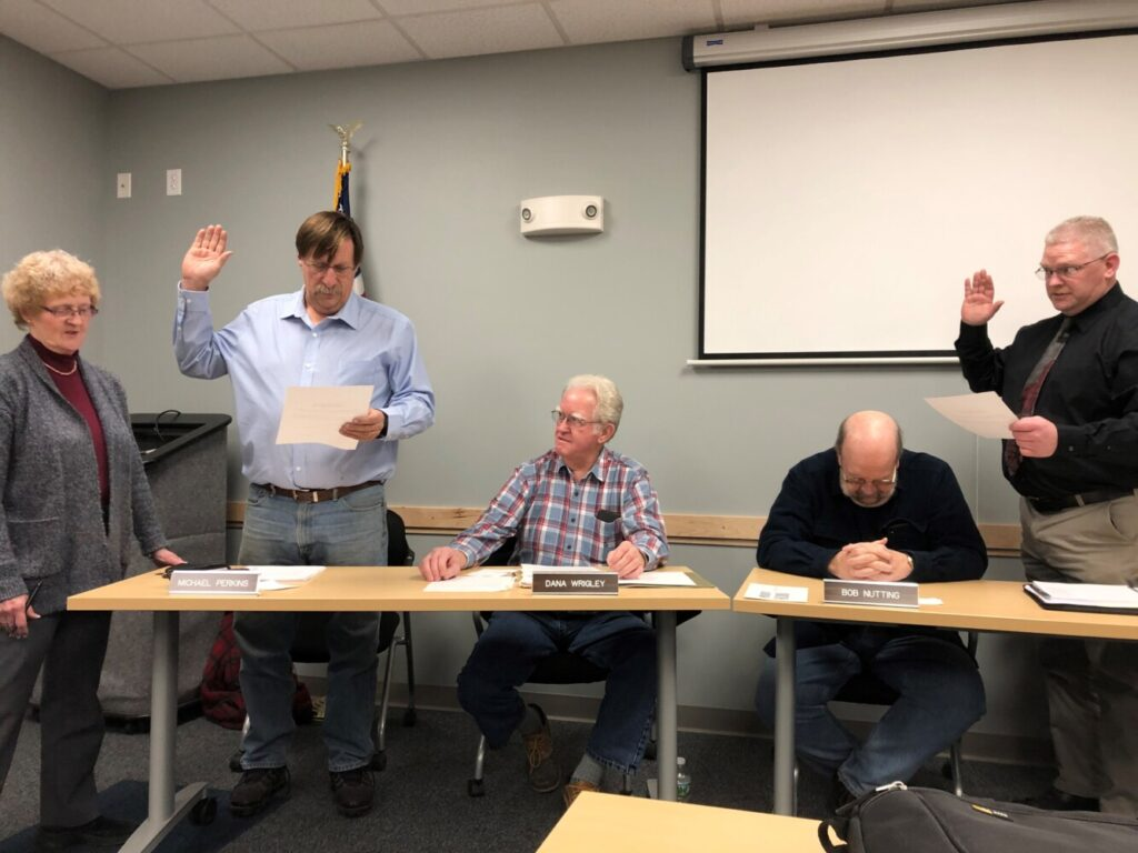 Deputy Town Manager Jan Porter, left, swears in reelected Councilor Mike Perkins, left, and first-time Councilor Dave Groder during the first Town Council meeting of the year Wednesday.