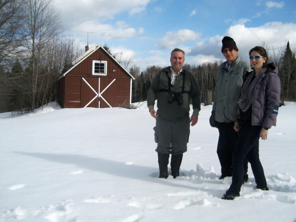 Jason Johnston, left, co-author of the paper on L.S. Quackenbush's journal on the changing seasons, Richard Primack and Caitlin McDonough MacKenzie pose in front of Quackenbush's barn in Oxbow, Maine.