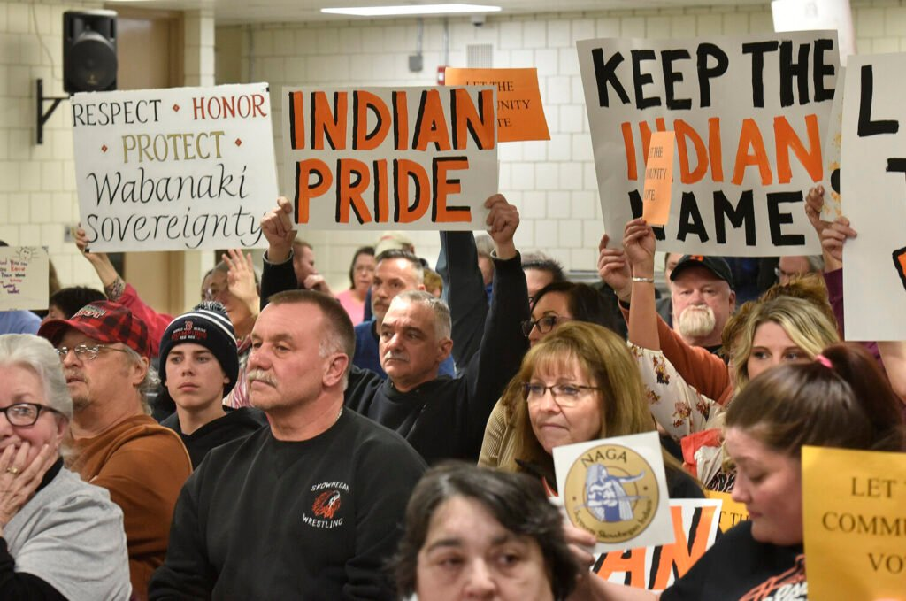 People for and against the use of the word Indian in School Administrative District 54 schools hold signs toward board members during a March 7, 2019, meeting in Skowhegan.