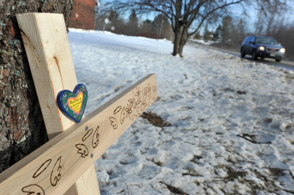 A homemade cross with three sets of angel wings and a personal message rests against a tree Wednesday, marking the location where three youths were killed Sunday morning in a car accident on the Hinckley Road in Clinton.