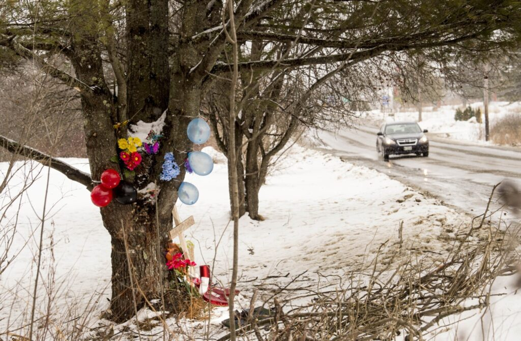 Mourners have left a cross and other items around a large pine tree on Hinckley Road in Clinton, where three youths died Sunday morning in a one-car accident.